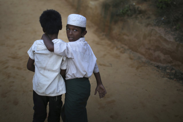 """A Rohingya Muslim boy looks back as he walks with his friend in Kutupalong refugee camp on Saturday, November 25, 2017, in Bangladesh. The United Nations and others have said the military's actions appeared to be a campaign of """"ethnic cleansing"""", using acts of violence and intimidation and burning down homes to force the Rohingya to leave their communities, with more than 600,000 Rohingya fleeing to Bangladesh. (Photo by Wong Maye-E/AP Photo)"""