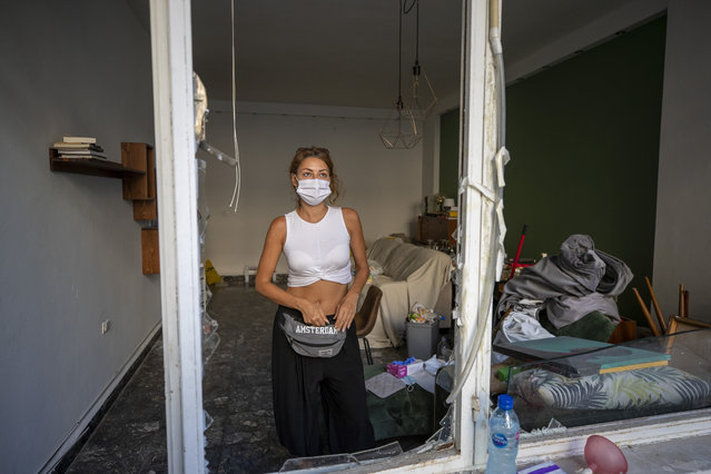 Sandrine Zeinoun, 34, poses for a photograph inside her destroyed apartment after Tuesday's explosion in the seaport of Beirut, Lebanon, Thursday, August 6, 2020. The gigantic explosion in Beirut on Tuesday tore through homes, blowing off doors and windows, toppling cupboards, and sent flying books, shelves, lamps and everything else. Within a few tragic seconds, more than a quarter of a million people of the Lebanese capital's residents were left with homes unfit to live in. Around 6,200 buildings are estimated to be damaged. (Photo by Hassan Ammar/AP Photo)