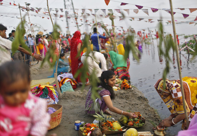 Women prepare to worship the Sun god Surya in the waters of the river Yamuna during the Hindu religious festival of Chatt Puja in New Delhi October 29, 2014. (Photo by Anindito Mukherjee/Reuters)