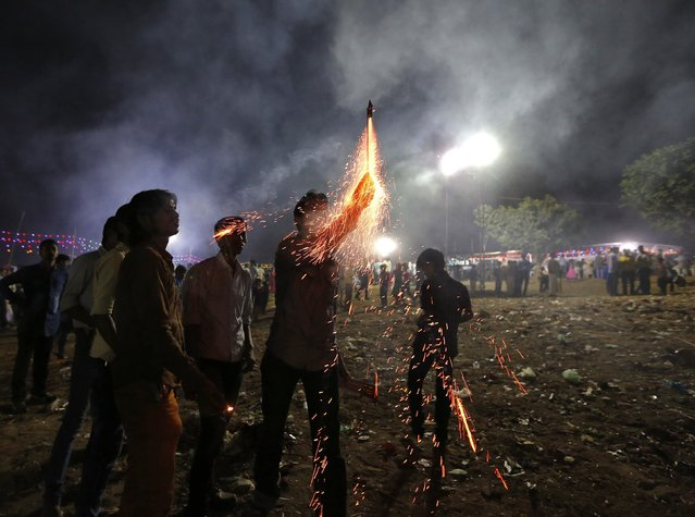 People light fireworks on the banks of the river Sabarmati during the Hindu religious festival of Chatt Puja in the western Indian city of Ahmedabad October 30, 2014. Hindu women fast for the whole day for the betterment of their family and the society during the festival. (Photo by Amit Dave/Reuters)