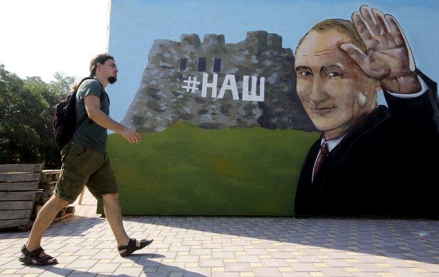 A man walks past graffiti depicting Russian President Vladimir Putin in Simferopol, Crimea, August 17, 2015. (Photo by Pavel Rebrov/Reuters)
