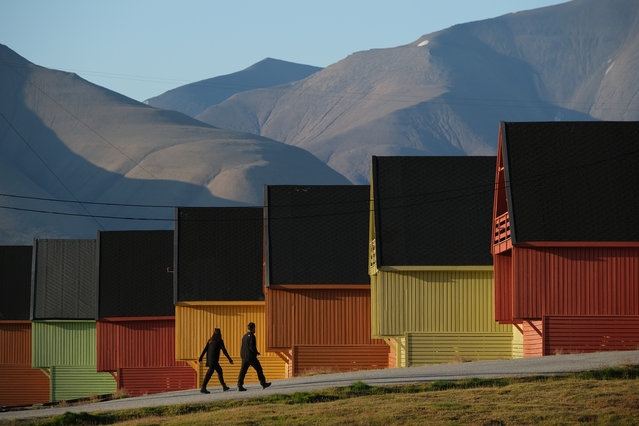 People walk past houses as mountains devoid of snow stand behind during a summer heat wave on Svalbard archipelago on July 30, 2020 in Longyearbyen, Norway. Svalbard archipelago, which lies approximately 1,200km north of the Arctic Circle, is currently experiencing a summer heat wave that set a new record in Longyearbyen on July 25 with a high of 21.7 degrees Celsius. Global warming is having a dramatic impact on Svalbard that, according to Norwegian meteorological data, includes a rise in average winter temperatures of 10 degrees Celsius over the past 30 years, creating disruptions to the entire local ecosystem. (Photo by Sean Gallup/Getty Images)