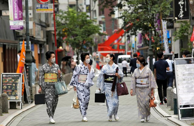 """Maki, Mayu, Koiku and Ikuko, who are geisha, wear protective face masks as they walk to a restaurant after attending a dance class, during the coronavirus disease (COVID-19) outbreak, in Tokyo, Japan. July 13, 2020. Ikuko fears an extended pandemic could prompt some geisha to quit. """"Now is the worst of the worst"""", she said. """"How are we going to get through? It'll take all of our body and soul"""". (Photo by Kim Kyung-Hoon/Reuters)"""
