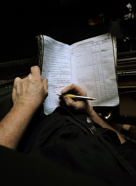 Puffing Billy steam engine driver Steve Holmes, 61, makes notes on the performance and problems of locomotive 6A in a daily log book following a day's work at Belgrave near Melbourne, October 17, 2014. (Photo by Jason Reed/Reuters)