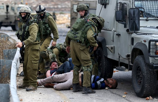 Israeli soldiers detain wounded Palestinian protesters during clashes near the Jewish settlement of Bet El, near the West Bank city of Ramallah October 7, 2015. (Photo by Mohamad Torokman/Reuters)