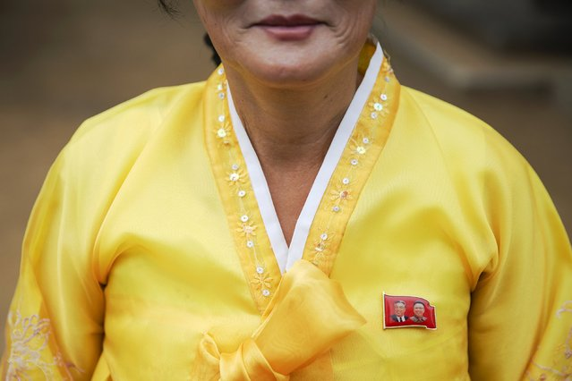 A woman in traditional clothes wears a pin showing North Korea's founder Kim Il-sung (L) and former leader Kim Jong-il, on her dress as she welcomes foreign reporters to a temple during a government organised tour just outside Pyongyang October 8, 2015. North Korea is getting ready to celebrate the 70th anniversary of the founding of its ruling Workers' Party of Korea on October 10. (Photo by Damir Sagolj/Reuters)