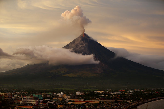 With Legazpi city in foreground, Mayon volcano erupts anew at sunset Thursday, January 25, 2018 in Albay province around 200 miles (340 kilometers) southeast of Manila, Philippines. The Philippine Institute of Volcanology and Seismology said lava flows had advanced more than a kilometer (0.6 miles) and superheated gas and volcanic debris known as pyroclastic flows had reached 5 kilometers (3 miles) from the crater in one area. Mayon's lava fountaining has flowed up to 3 kilometers (1.86 miles) from the crater in a dazzling but increasingly dangerous eruption. (Photo by Bullit Marquez/AP Photo)