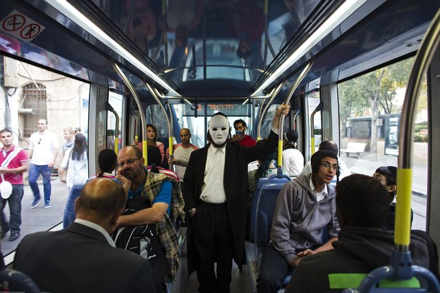 Passengers, one wearing a mask, ride a light rail tram in Jerusalem November 11, 2014. If there has been a constant target of Palestinian attacks during weeks of unrest in Jerusalem, it is the city's Light Rail, a sleek tram that snakes through downtown, past the ancient walls of the Old City, symbolically uniting the Jewish West and the Arab East, an area Israel captured in a 1967 war. (Photo by Ronen Zvulun/Reuters)