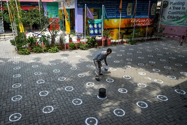 A worker draws marks on the ground for social distancing at a school in Lahore on September 13, 2020, following the government's announcement to reopen educational institutes starting from September 15, nearly six months after the spread of the Covid-19 coronavirus. (Photo by Arif Ali/AFP Photo)