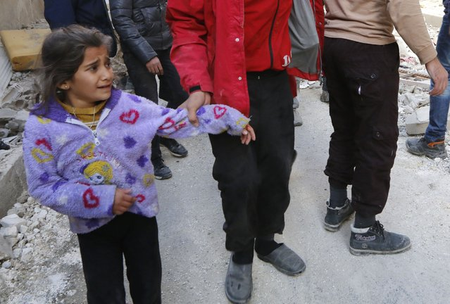A girl reacts as a man holds her hand at site hit by what activists said were airstrikes by forces loyal to Syria's President Bashar al-Assad in Raqqa, eastern Syria, which is controlled by the Islamic State November 27, 2014. (Photo by Nour Fourat/Reuters)