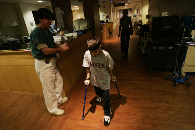 Rakan Hassan, 12, ambles about the halls of Spaulding Rehabilitation Hospital in Boston, Massachusetts, on January 11, 2006. Rakan's parents were shot and killed and he was gravely wounded by U.S. soldiers in an accidental shooting on January 18, 2005 in the northern Iraqi city of Tal Afar. The incident was widely publicized, and ultimately led to Rakan's treatment in Boston. With nerve damage to his abdomen and spine, doctors thought Rakan might never walk again, but an intensive physical therapy regimen has brought back the use of his legs and he can now walk with assistance. (Photo by Chris Hondros/The Atlantic)