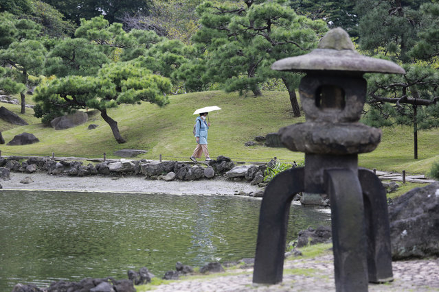 A visitor wearing face mask to protect against the spread of the coronavirus walks at the Kyu Shiba Rikyu Garden in Tokyo, Tuesday, October 13, 2020. (Photo by Koji Sasahara/AP Photo)