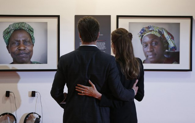 Special Envoy of the United Nations High Commissioner for Refugees, actress Angelina Jolie (R), and her partner actor Brad Pitt, look at photographs of victims of violence at the End Sexual Violence in Conflict summit in London, in this June 12, 2014 file photo. (Photo by Lefteris Pitarakis/Reuters)