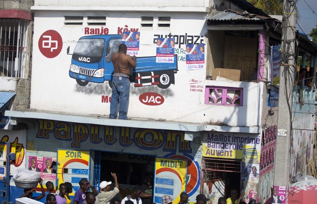 In this September 21, 2016 photo, a man pastes a campaign poster showing Haiti's ousted President Jean Bertrand-Aristide with presidential candidate Maryse Narcisse as the two campaign in the area in Port-au-Prince, Haiti. Although Aristide said he wouldn't focus on politics after he returned from exile in 2011, the twice-elected, twice-ousted leader has been campaigning for Maryse Narcisse, the presidential candidate for his Fanmi Lavalas party. Haiti will hold elections on October 9. (Photo by Dieu Nalio Chery/AP Photo)