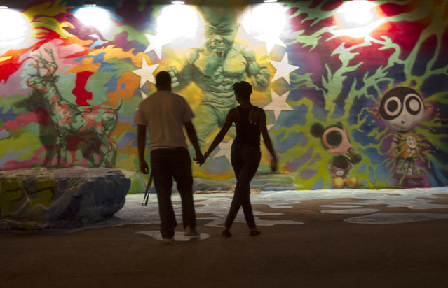 Jerel Rodriguez, left, 23, and Monique Bell, 22, both of Miami, look at wall art by Ron English, Wednesday, December 3, 2014, at Wynwood Walls in Miami. Art Basel Miami Beach, the contemporary art fair that doesn't officially begin until Thursday has already has overtaken parts of Miami. (Photo by Wilfredo Lee/AP Photo)