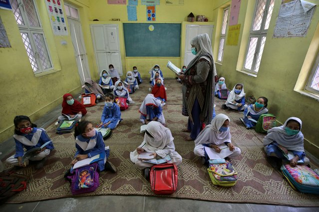 Students attend a class during the first day of primary school, after the resumption of classes in Peshawar, Pakistan, 30 September 2020. The Pakistani government on 28 September reopened educational institutions to resume primary classes as part of a phased reopening of schools. (Photo by Bilawal Arbab/EPA/EFE)