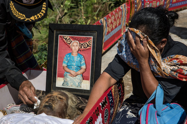 A woman cries in front of the corpse of Marta Ratte Limbong during the Ma'Nene ritual in Ba'Tan Village, Toraja, South Sulawesi, Indonesia on August 23, 2016. Locals believe dead family members are still with them, even if they passed away hundreds of years ago. (Photo by Agung Parameswara/The Washington Post)
