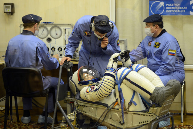A crew member of the next expedition to the ISS, US astronaut Christopher Cassidy checks his space suit prior to the launch of the the Soyuz TMA-08M spacecraft at the Baikonur Cosmodrome, on March 28, 2013. (Photo by Ramil Sitdikov/AFP Photo/The Atlantic)