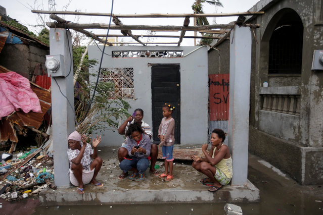 Women sit at the entrance of a house damaged by Hurricane Matthew in Les Cayes, Haiti, October 5, 2016. (Photo by Andres Martinez Casares/Reuters)