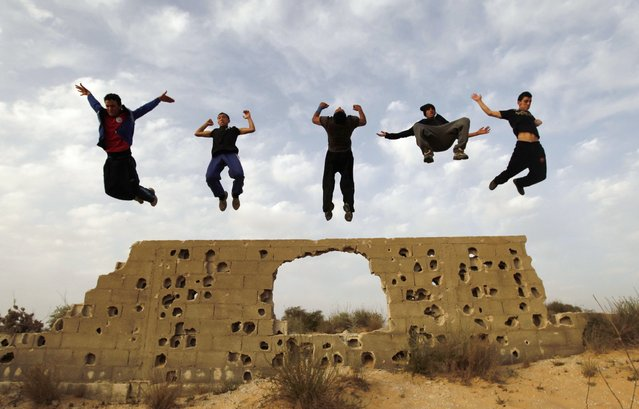Palestinian youths practice their parkour skills in KhanYounis, southern Gaza Strip, Sunday, March 31, 2013. Parkour is a physical discipline of movement focused on overcoming obstacles. Training is held at cemeteries in KhanYounis. (Photo by Hatem Moussa/AP Photo)