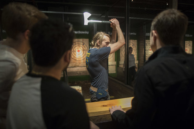 "In this March 3, 2018, photo, an ""axepert"", center, gives contestants instruction on hatchet throwing techniques and the rules of the game at the Kick Axe Throwing venue in the Brooklyn borough of New York. Kick Axe Throwing is the first bar in New York City to pick up on a nationwide trend of ax throwing. (Photo by Mary Altaffer/AP Photo)"