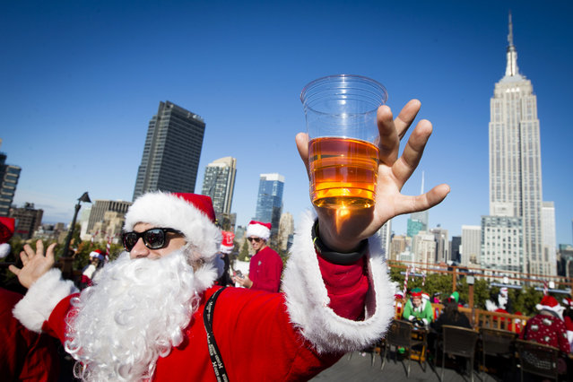 A man dressed as Santa Claus holds a beer as he and others participate in SantaCon on a rooftop bar Saturday, December 13, 2014, in New York. (Photo by John Minchillo/AP Photo)
