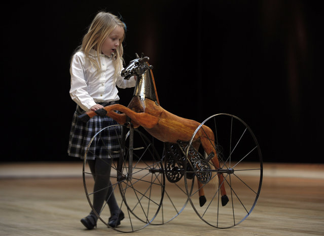 """A girl touches a steel and stained child's tricycle from early 20th century modeled as a branding horse, as she poses for the photographers during a press preview of a themed auction that features the animal as artistic inspiration, entitled the """"Creatures Great and Small"""", in London, Monday, December 15, 2014. (Photo by Lefteris Pitarakis/AP Photo)"""