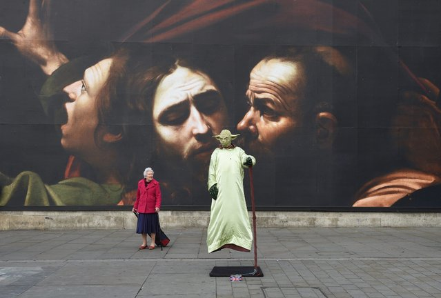 """A street performer wearing a dress depicting """"Yoda"""" stands in front of a giant poster, a detail of a painting by Italian artist, Michelangelo Merisi da Caravaggio: """"The Taking of Christ"""", 1602 outside the National Gallery in London, Britain, 12 October 2016. (Photo by Facundo Arrizabalaga/EPA)"""