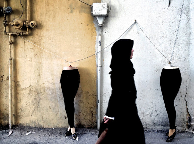 An Iranian woman walks past mannequins locked to a gas pipe in northern Tehran on December 15, 2014. (Photo by Behrouz Mehri/AFP Photo)