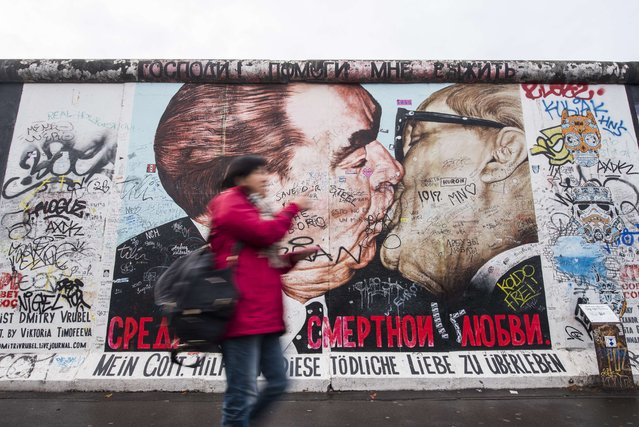"""A tourist walks past the graffiti-covered mural painting """"My God, Help Me to Survive This Deadly Love"""" by Russian painter Dmitri Vrubel , depicting the kiss between then Soviet leader Leonid Brezhnev (L) and East German leader Erich Honecker at the East Side Gallery, a stretch of the Berlin wall, in Berlin on November 6, 2015. A quarter-century after the fall of the Berlin Wall, the city announced it would build a barrier to protect the longest surviving stretch from a sharp rise in vandalism. (Photo by John Macdougall/AFP Photo)"""