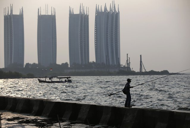 A man fishes along a seawall in north Jakarta November 12, 2014. Picture taken November 12, 2014. (Photo by Darren Whiteside/Reuters)