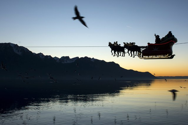 """Santa Claus waves to the crowd from his flying sleigh drawn by reindeer over the Geneva Lake and in front of the Swiss and French alps at sunset during the 20th edition of the Christmas Market in Montreux, Switzerland, 23 December 2014. Santa Claus is """"flying"""" with the aid of a cable above the market and the lake on a distance of 385 meters. (Photo by Jean-Christophe Bott/EPA)"""