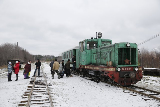People wait to board a train in the village of Ugolnaya, in Sverdlovsk region, Russia, October 16, 2015. Many people who live along the Alapayevsk narrow-gauge railway do not earn enough to buy a car and so depend on the railway for transportation. Train tickets cost between 10 and 50 cents. (Photo by Maxim Zmeyev/Reuters)