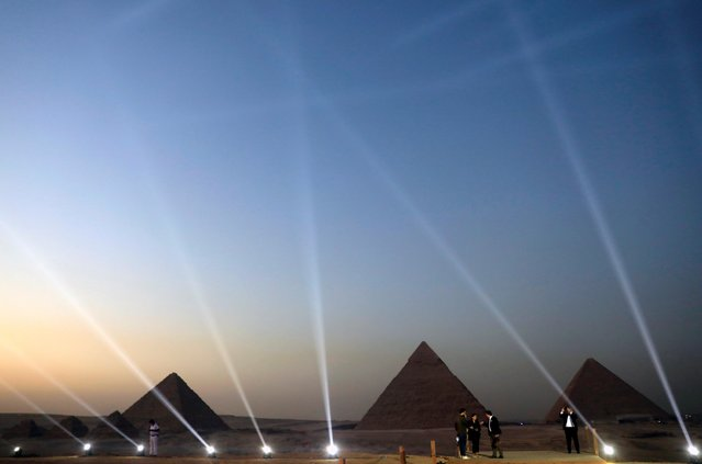 """People take pictures in front of the Great Pyramids during the opening of a new restaurant called """"9 Pyramids Lounge"""" by Orascom Pyramids Entertainment (OPE) in Giza, Egypt on October 20, 2020. (Photo by Amr Abdallah Dalsh/Reuters)"""