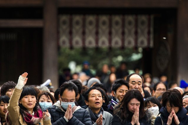 People pray and throw offerings for the upcoming year at the Shinto Meiji Shrine in Tokyo January 1, 2015. (Photo by Thomas Peter/Reuters)