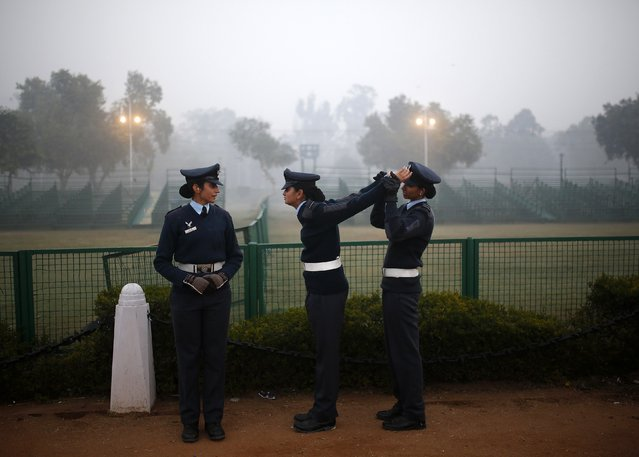 An Indian Air Force soldier (R) stretches the arms of her colleague during the rehearsal for the Republic Day parade on a cold and foggy winter morning in New Delhi December 30, 2014. India will celebrate its annual Republic Day on January 26. (Photo by Ahmad Masood/Reuters)