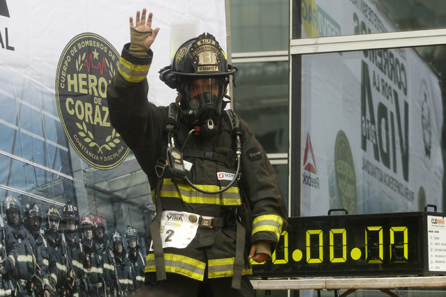 """A firefighter waves before climbing up the 1800 steps of the Costanera Centre Tower in Santiago as part of the """"Race for Life"""" aimed at encouraging organ donation in Chile, on October 16, 2016. (Photo by Claudio Reyes/AFP Photo)"""