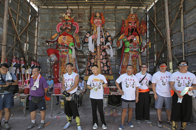 Villagers stand in front of the King of ghosts on the outlying Cheung Chau island in Hong Kong to celebrate the Bun Festival Tuesday, May 22, 2018. (Photo by Kin Cheung/AP Photo)