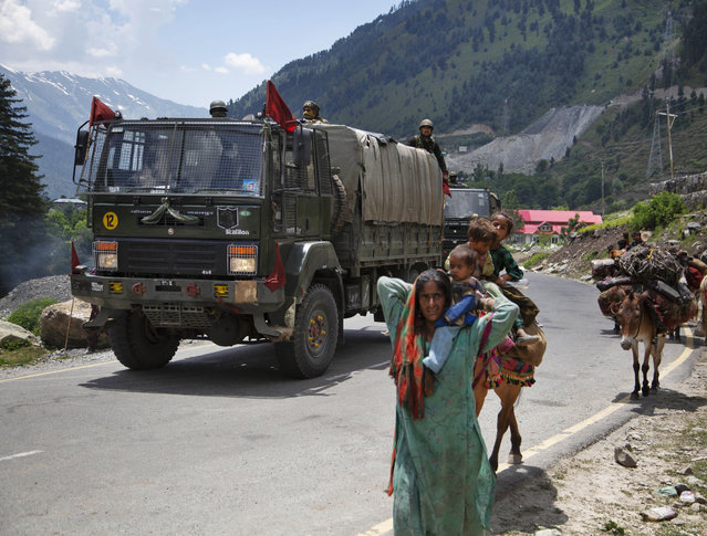 Kashmiri Bakarwal nomads walk as an Indian army convoy moves on the Srinagar- Ladakh highway at Gagangeer, north-east of Srinagar, India, Wednesday, June 17, 2020. Indian security forces said neither side fired any shots in the clash in the Ladakh region late Monday that was the first deadly confrontation on the disputed border between India and China since 1975. China said Wednesday that it is seeking a peaceful resolution to its Himalayan border dispute with India following the death of 20 Indian soldiers in the most violent confrontation in decades. (Photo by Mukhtar Khan/AP Photo)
