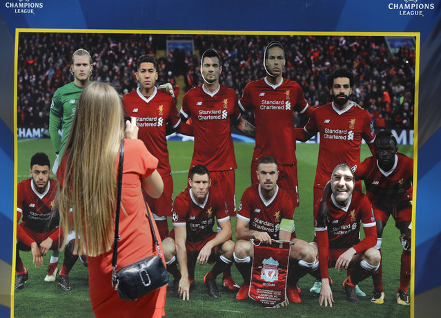 A woman takes a photo of a banner depicting Liverpool team at a fan-zone in Kiev, Ukraine, Thursday, May 24, 2018. (Photo by Sergei Grits/AP Photo)