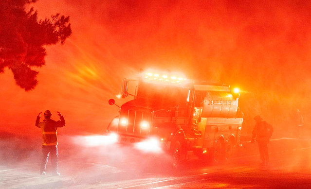 Firefighters spray down flames on the side of Interstate 210 in Sylmar, California on January 19, 2021. Dozens of fires ignited as high winds and low humidity continue to spread throughout the state. (Photo by Josh Edelson/AFP Photo)