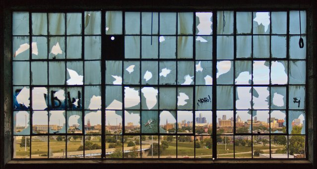 """""""Broken City"""". Taken from inside one of the many abandoned factories in the city, a distant view of Detroit's skyline displaying the many struggles and hardships the city has encountered. Location: Detroit, Michigan USA. (Photo and caption by Ramiro Zarate/National Geographic Traveler Photo Contest)"""