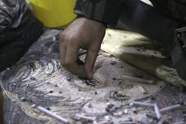 """Raad, 37, works on a mosaic artwork, copied from an original painting, in a workshop in Kafranbel town in the Idlib governorate January 17, 2015. Raed is a """"Free Syrian Army"""" fighter that works in the workshop. (Photo by Khalil Ashawi/Reuters)"""