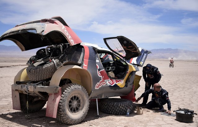 Peugeot driver Stephane Peterhansel and copilot Jean-Paul Cottret of France repair their car during the 9th stage of the Dakar Rally 2015 from Iquique to Calama January 13, 2015. (Photo by Franck Fife/Reuters)