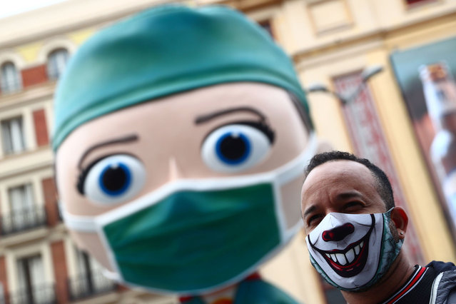 A man wearing a protective face mask poses for pictures next to an oversized model of a health worker amid the outbreak of the coronavirus disease (COVID-19), in Madrid, Spain on September 24, 2020. (Photo by Sergio Perez/Reuters)