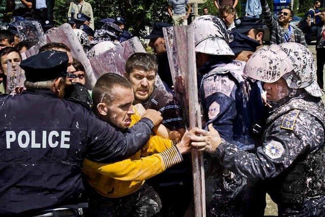 Police, who were splashed with paint, scuffle with hard line opposition members in Pristina, Kosovo,  protesting an agreement by lawmakers to normalize relations with Serbia, on June 27, 2013. (Photo by Visar Kryeziu/Associated Press)
