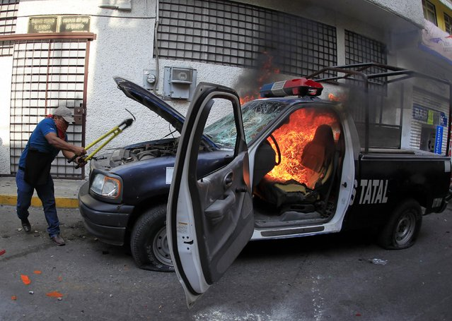 A demonstrator takes part in destroying a burning police patrol vehicle during a protest by relatives of the 43 missing students from the Ayotzinapa Teacher Training College outside the federal court in Chilpancingo, in the Mexican state of Guerrero, January 19, 2015. (Photo by Jorge Dan Lopez/Reuters)