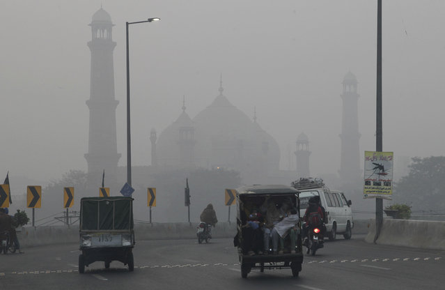 Motorists drive through a road close to historical Badshahi mosque while dense smog engulf the neighborhood of Lahore, Pakistan, Saturday, November 5, 2016. Thick smog has engulfed several cities in central Pakistan for few days, causing, breathing problems, road accidents and disruption of flight and train scheduled as well as the closure of the sections of the main motorways. (Photo by K.M. Chaudary/AP Photo)