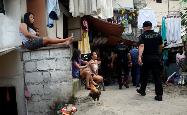 Residents look at policemen conducting an anti-drugs operation in Mandaluyong, Metro Manila in the Philippines, November 10, 2016. (Photo by Erik De Castro/Reuters)