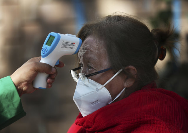 A woman gets her temperature taken as she waits to get the AstraZeneca vaccine against COVID-19 in the Magdalena Contreras area of Mexico City, Monday, February 15, 2021, as Mexico begins to vaccinate people over age 60 against the new coronavirus. (Photo by Marco Ugarte/AP Photo)